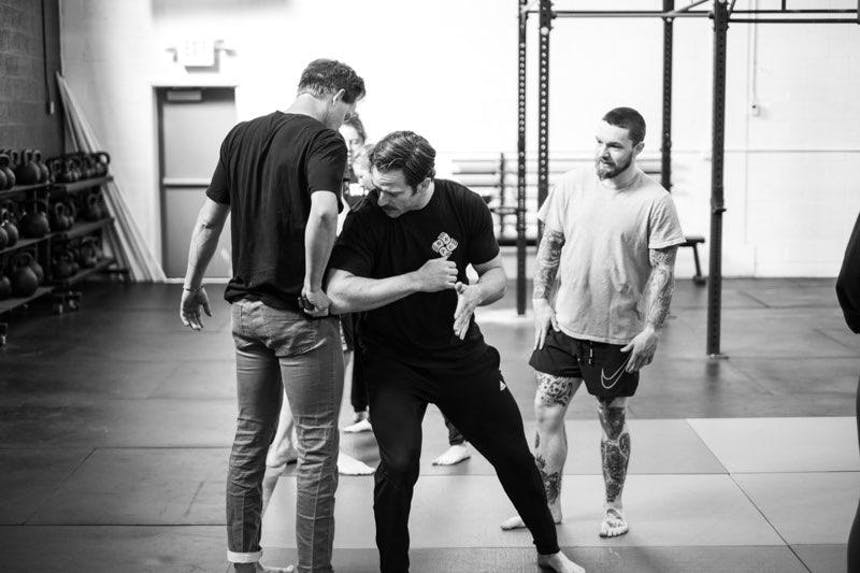 black and white image of three men working on drills in a gym for self defense