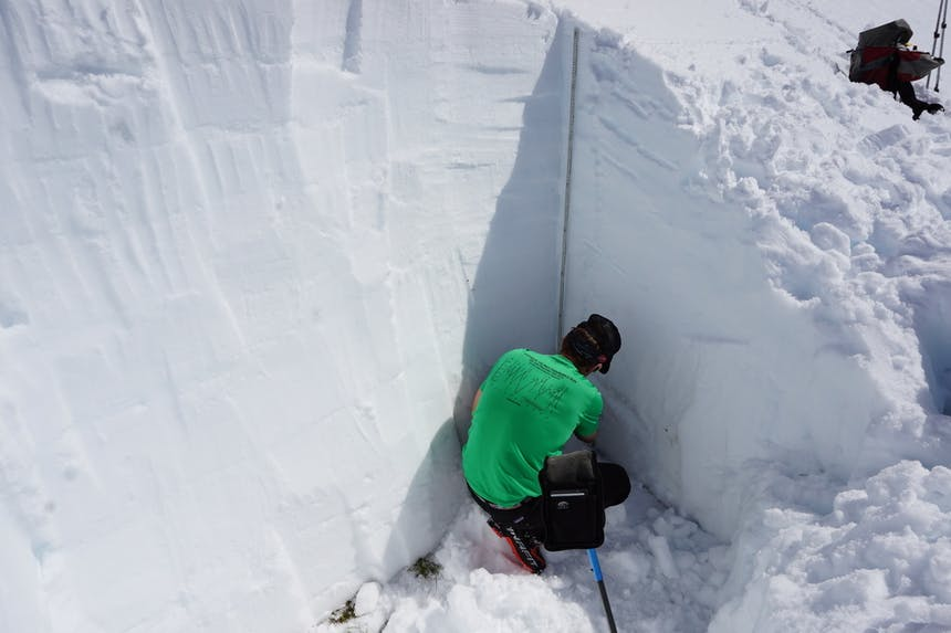 a man wearing a green t-shirt and black snow pants crouched down reading the snowpack