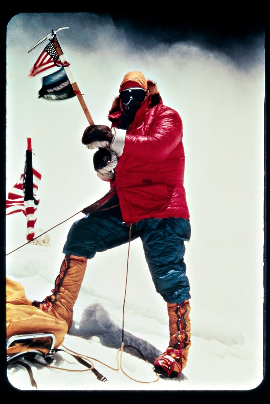 an old image of a mountaineer at the summit wearing a thick red jacket, blue snow-ants and tall lace up brown boots holding flags
