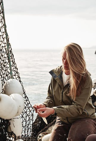 a blonde haired woman sitting on the side of a boat working with a fishing net wearing a white shirt under a brown rain jacket with brown work pants