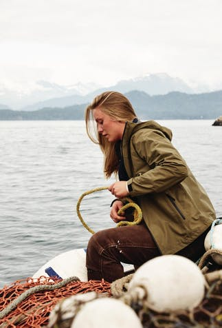 blonde woman sitting on the side of a boat in the water with mountains in the distance pulling in a yellow rope