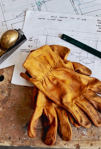 paper with diagrams on a desk with a pair of filson leather gloves