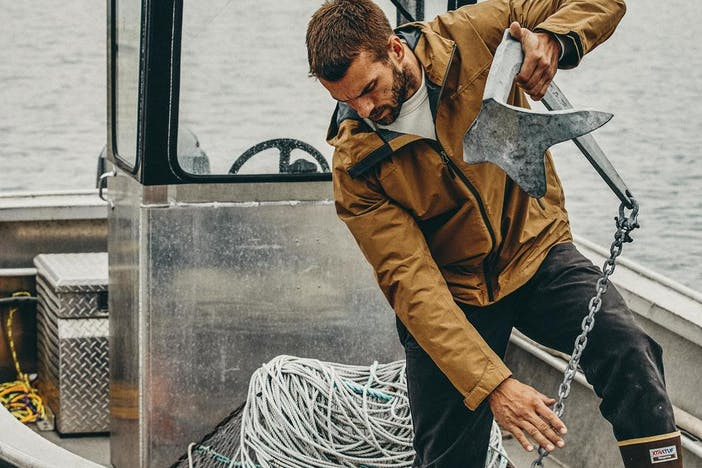 a brunette man with a beard in the front of a small aluminum boat pulled out the anchor to toss overboard