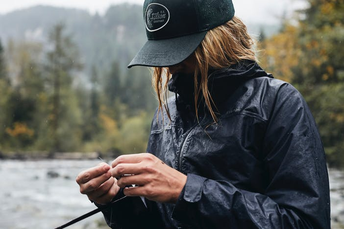 a close up of a blonde wearing a dark green ball cap, navy rain jacket and is working on he fly hook and line along a river