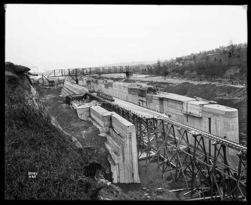 Image of ballard lock a large concrete structure is bisected by a wooden and metal structure rising out of a river