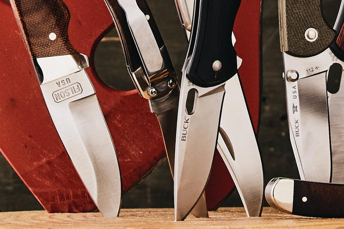 an assortment of knives, fixed blades, black and brown handles stuck into a log in front of a red and wood handled axe