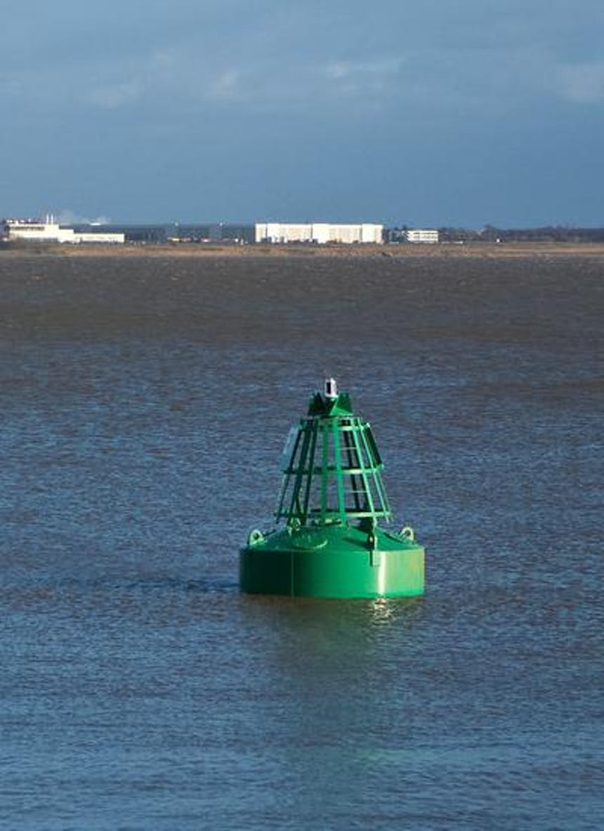 an image from a boat of a green buoy