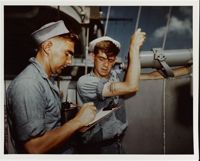 two seamen one standing at a large telescope and one taking notes on a clipboard