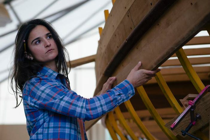 brunette woman in blue plaid scout shirt touching a wooden boat being built