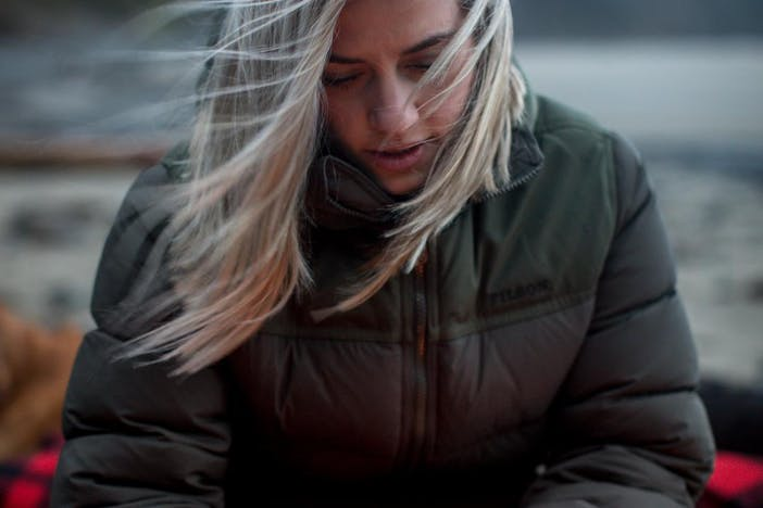 blonde woman sitting in front of fire on beach wearing brown puffy coat