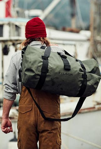 a long haired brunette man walking down a dock lined with boats away from the camera wearing brown overalls, a light blue shirt and red beanie as he hold a large green dry duffle bag over his shoulder