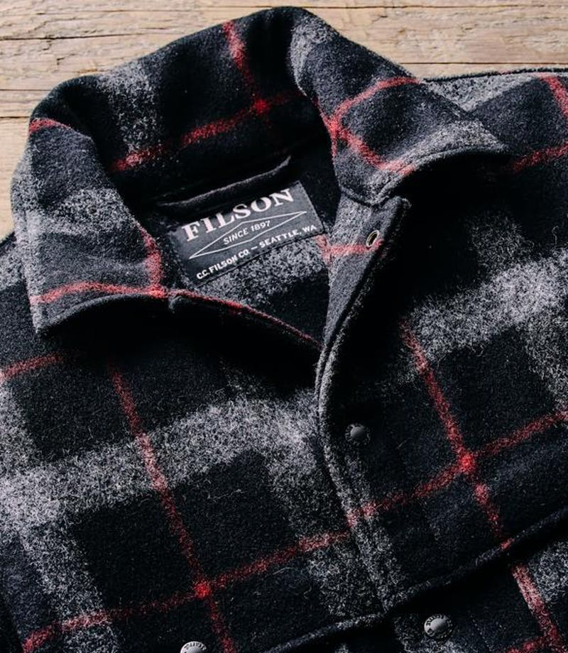 a lay down of a black, white and red flannel pattern Filson Mackinaw Wool Cape Coat on rustic wood
