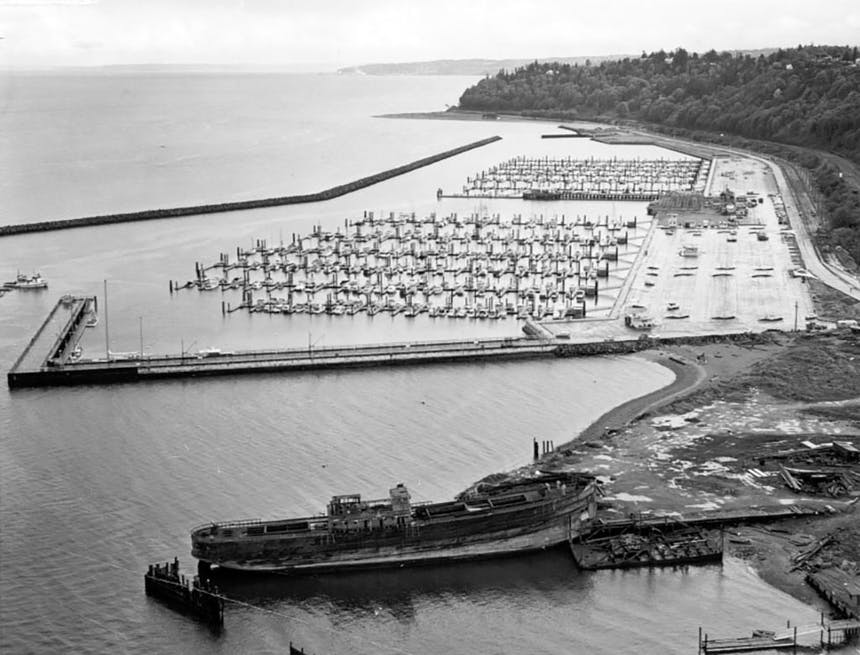 two square groupings of ships at harbor in a protected marina with a large wooden ship docked outside the marina
