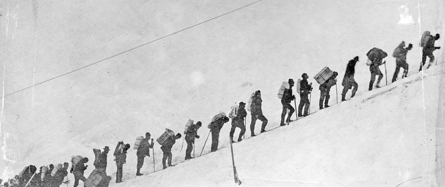 LINE OF PEOPLE WALKING UP A STEEP SLOPE IN THE SNOW WITH mountain climbing gear on their backs