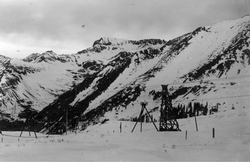 Black and white image of wooden tower structures in snowy field with snow covered mountains in background