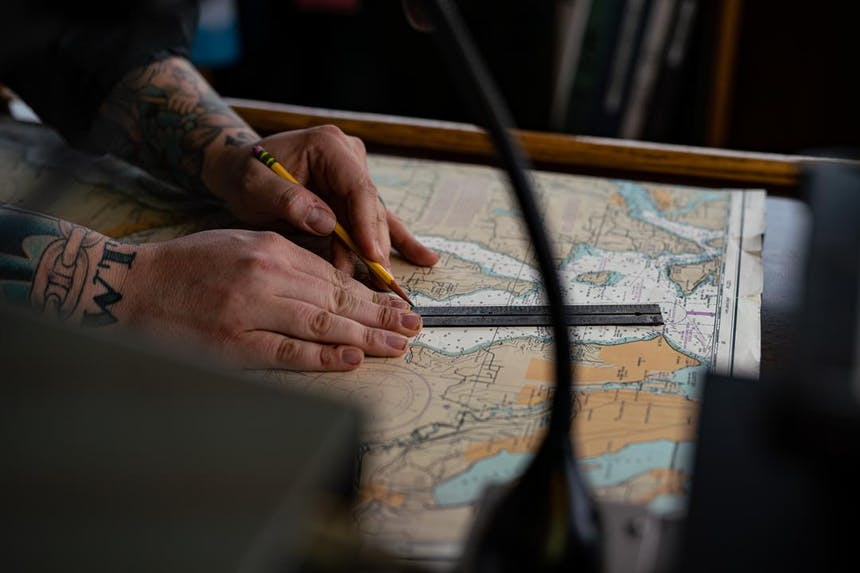 a side view of a sailor working on planning out a route using a nautical chart, pencil and ruler