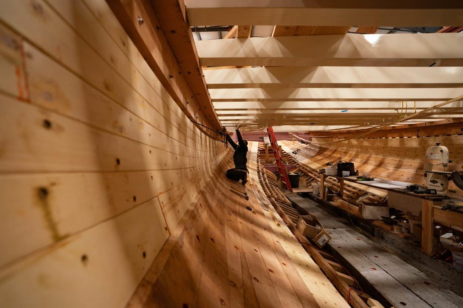 man working under the deck of a wooden ship being built