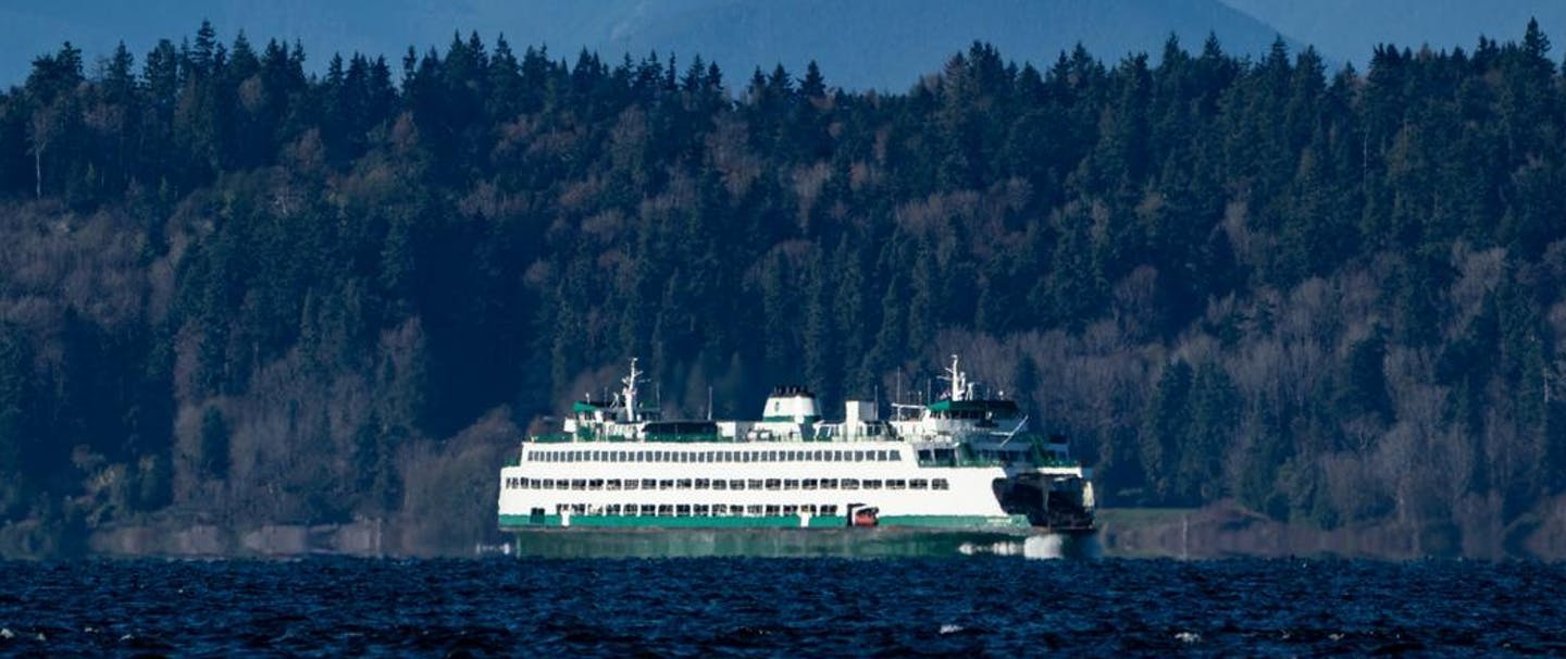 image from afar capturing the landscape of a Puget Sound ferry crossing the water with mountains towering overhead
