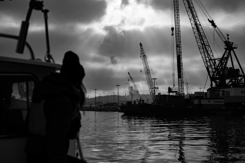 a black and white shot from the hull of the boat looking towards the seattle shipping yard