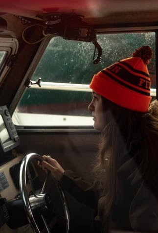 a young girl with long brown hair wearing a bright orange beanie driving a boat