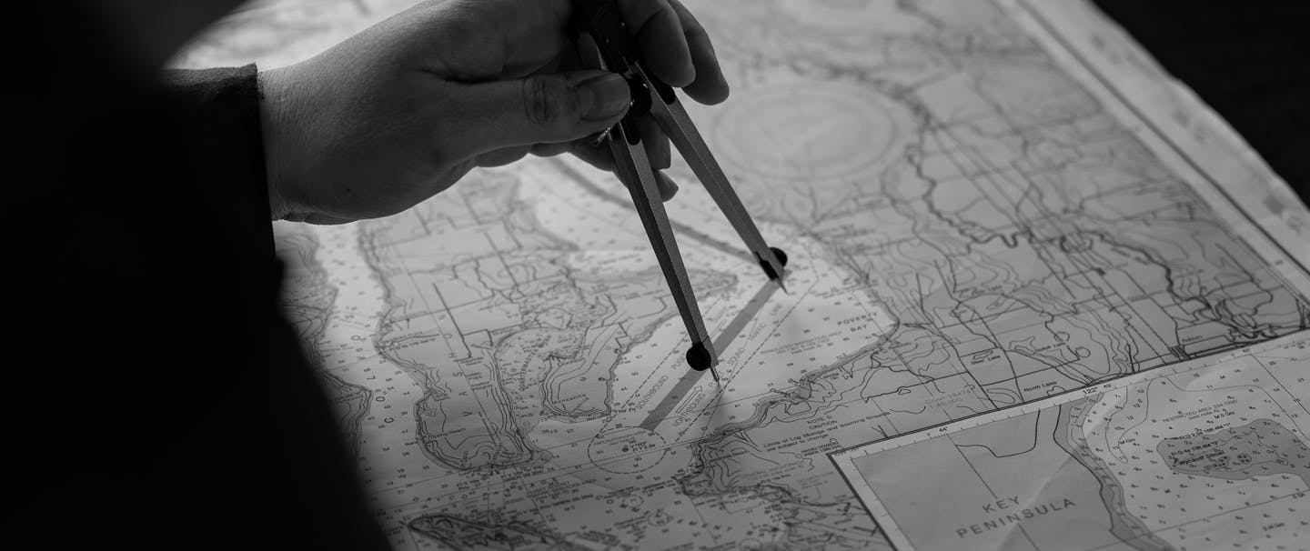 a black and white shot from behind a sailor mapping out a route with a compass on a nautical chart