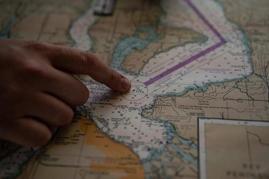 an index finger pointing to a spot on a nautical chart