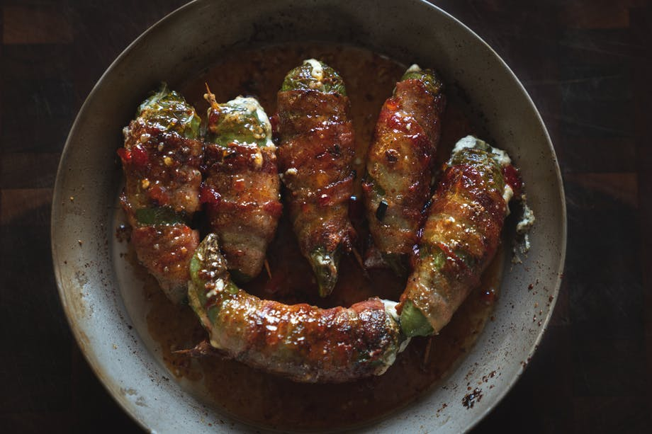 dish of candied, bacon wrapped jalapeno poppers in circular metal dish