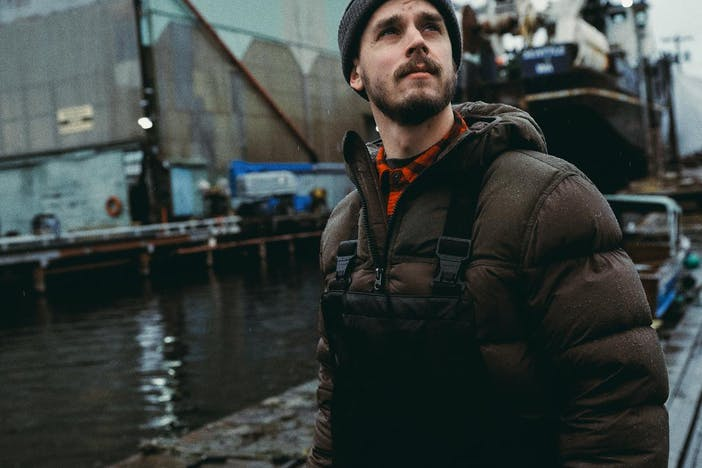 man in puffy brown coat and brown beanie standing on dock in front of large structure and machinery