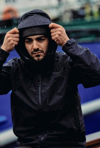 a dark haired man with facial hair pulling on his navy rain jacket hood