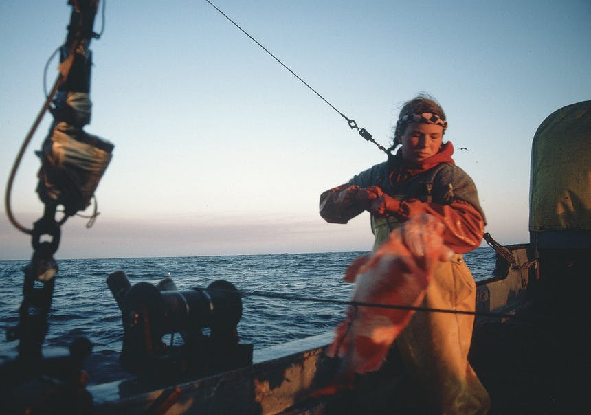 girl on fishing vessel at sunset working
