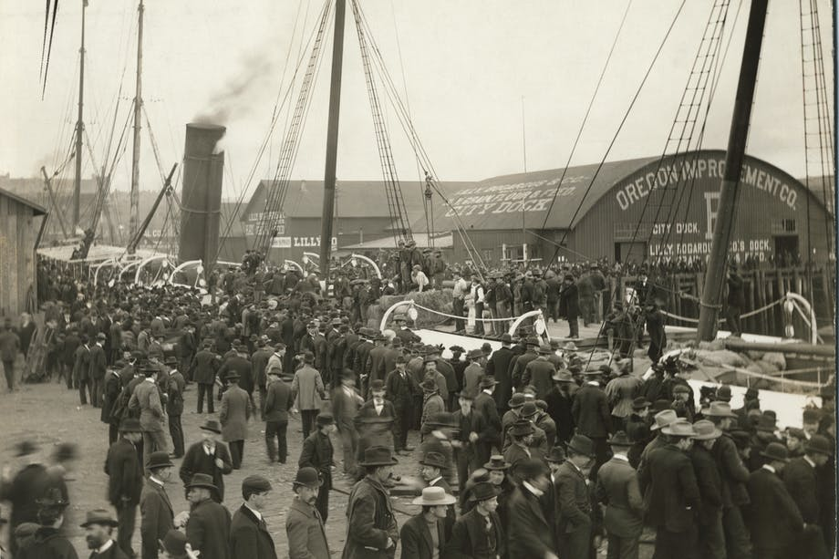 vintage black and white image of large crowd of people all in suits at the oregon improvement co. facility