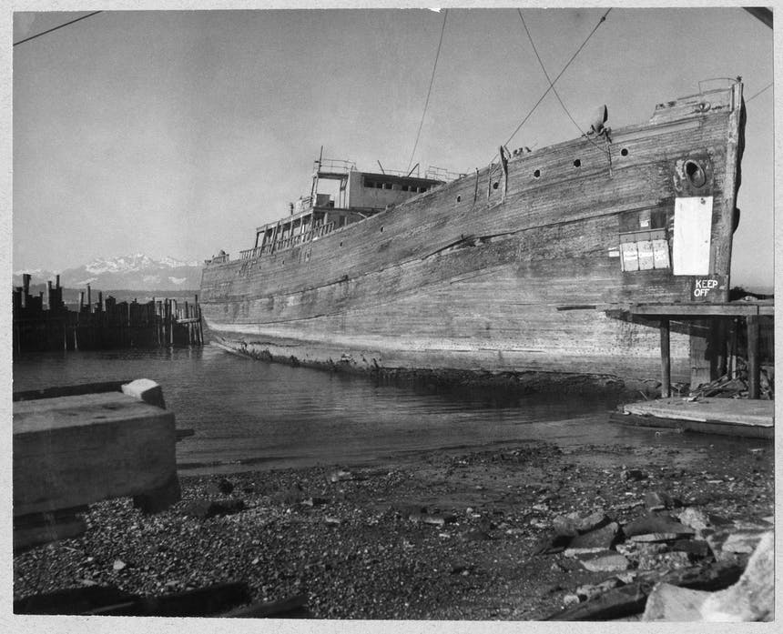 large derelict wooden ship docked on a black sandy/muddy beach