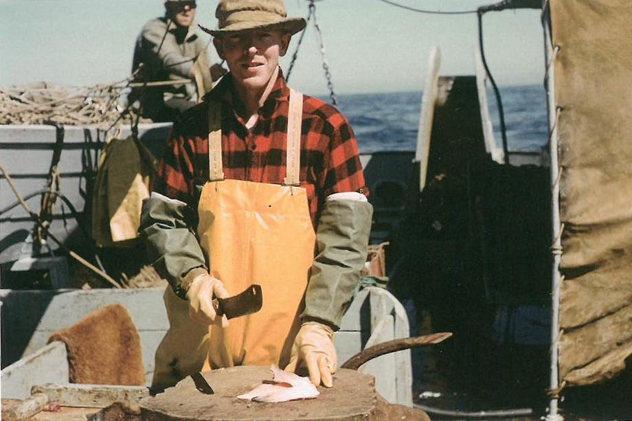 man on boat in red plaid shirt and tan apron prepares a halibut stomach as bait on a wooden surface