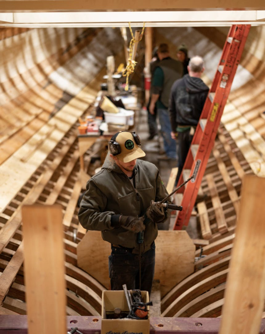 shipwrights work on the wooden hull of a large vessel