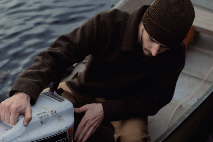man in brown jacket and beanie inspects piece of machinery on a boat in water