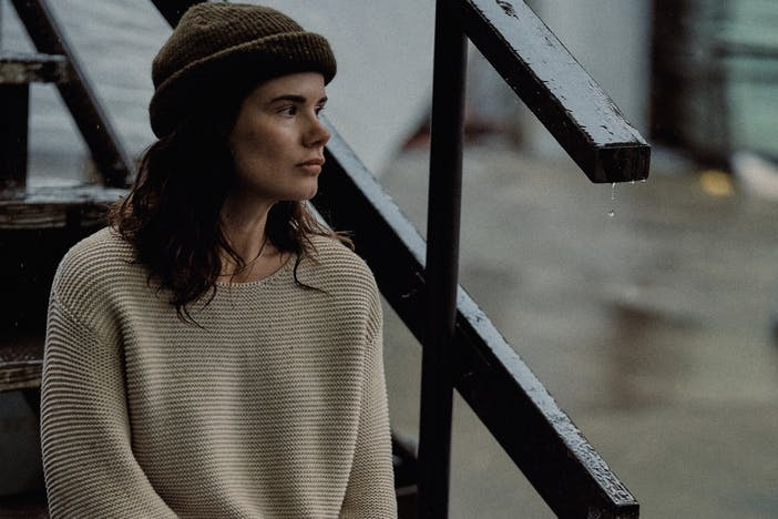 brunette woman in beige knitted sweater and olive beanie sitting on wet wooden staircase outside