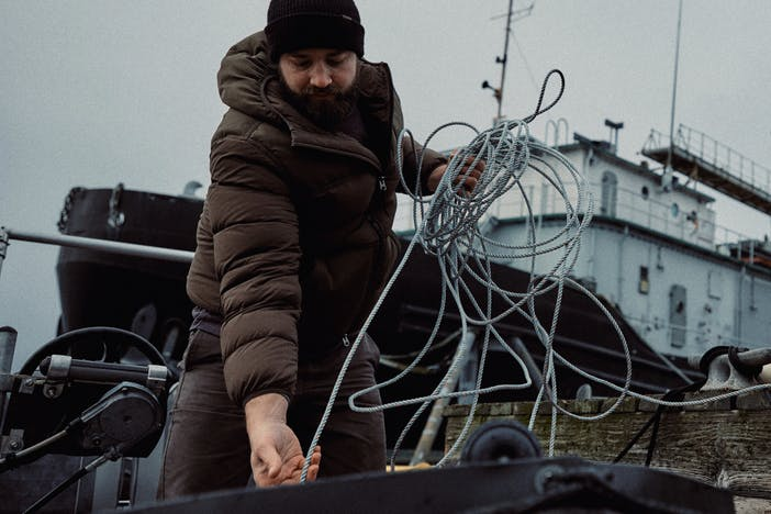 man in puffy brown coat pulling a line in with a ship in the background