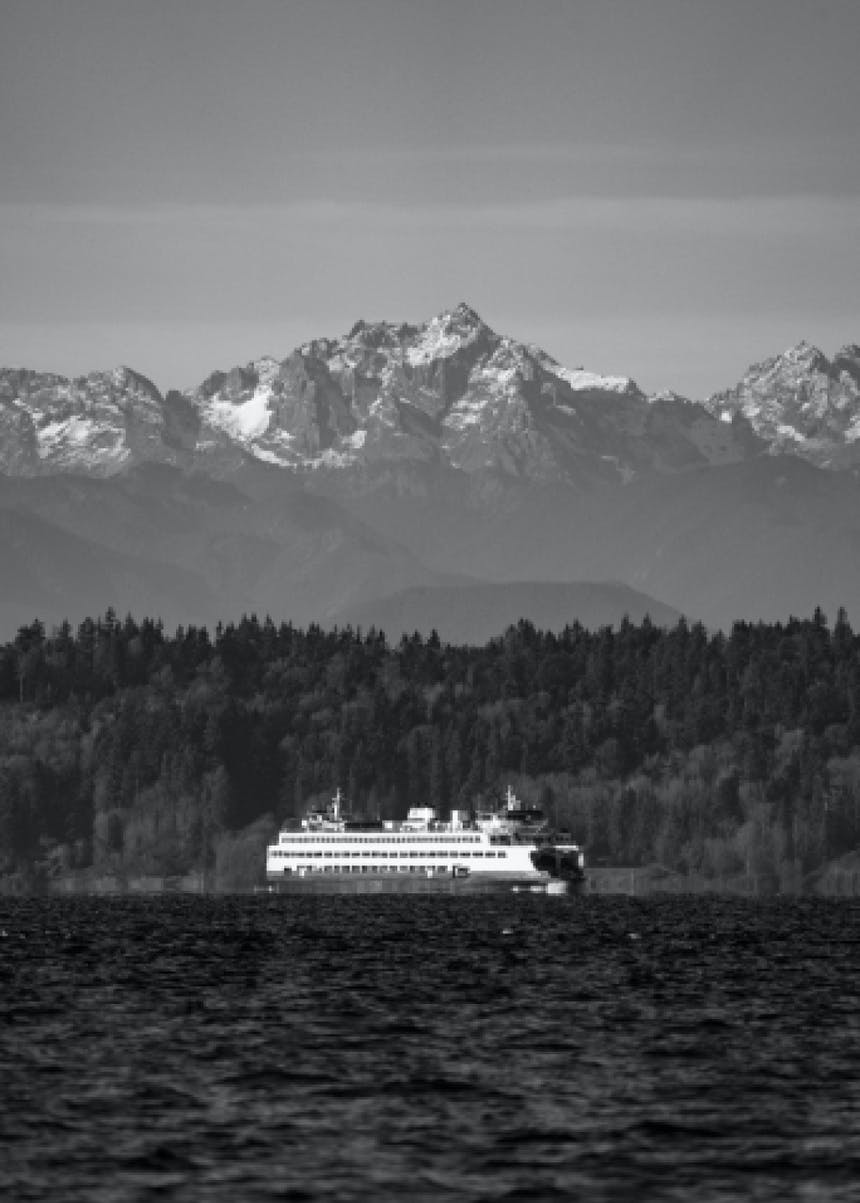 black and white image from afar capturing the landscape of a Puget Sound ferry crossing the water with mountains towering overhead