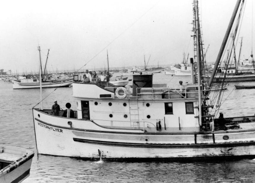 black and white image of boats anchored in a harbor. Small double deck fishing vessel named