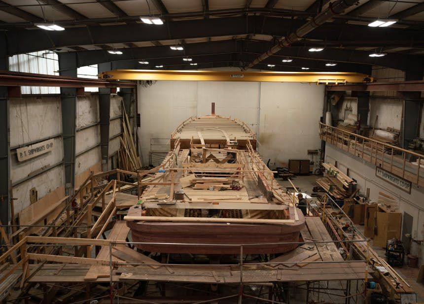 large wooden boat being built at a dry dock workshop facility