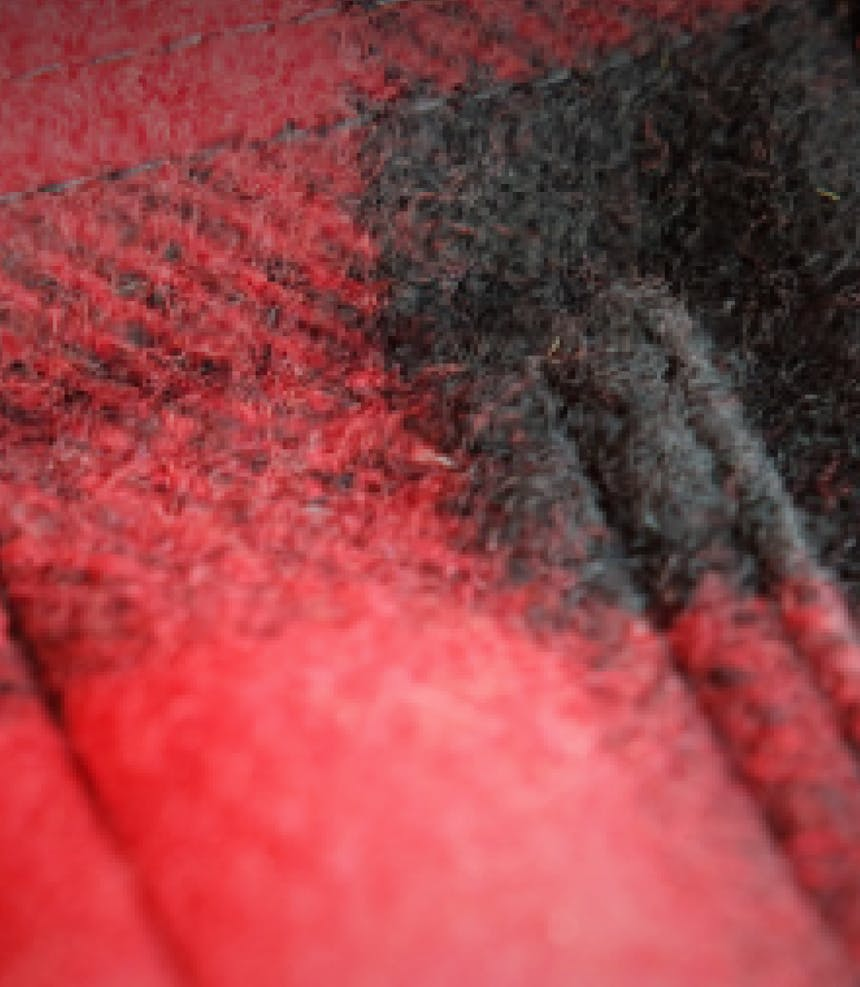 a close up view of fibers on a red and black mackinaw wool vest