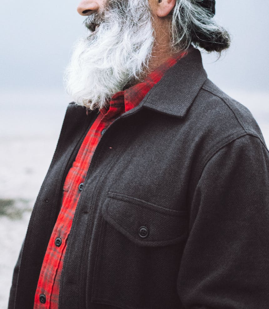 a side view of a grey and white haired and bearded man wearing a red and brown flannel shirt under a black wool button up jacket