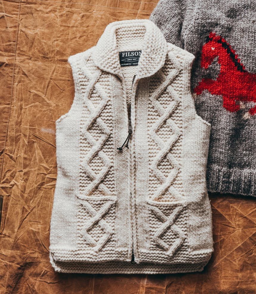 a top down view of a white wool knit vest and a back of a grey wool sweater with a red horse knit into it on top of a canvas backdrop