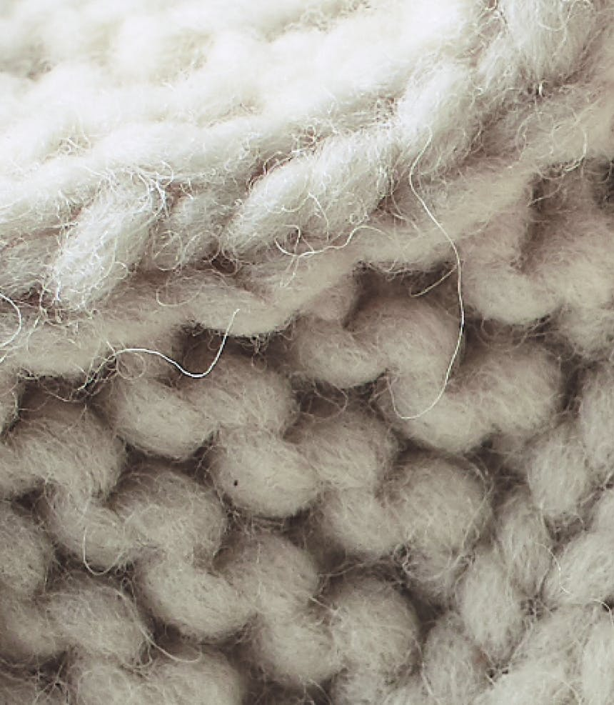 a close up view of white knit wool sweater