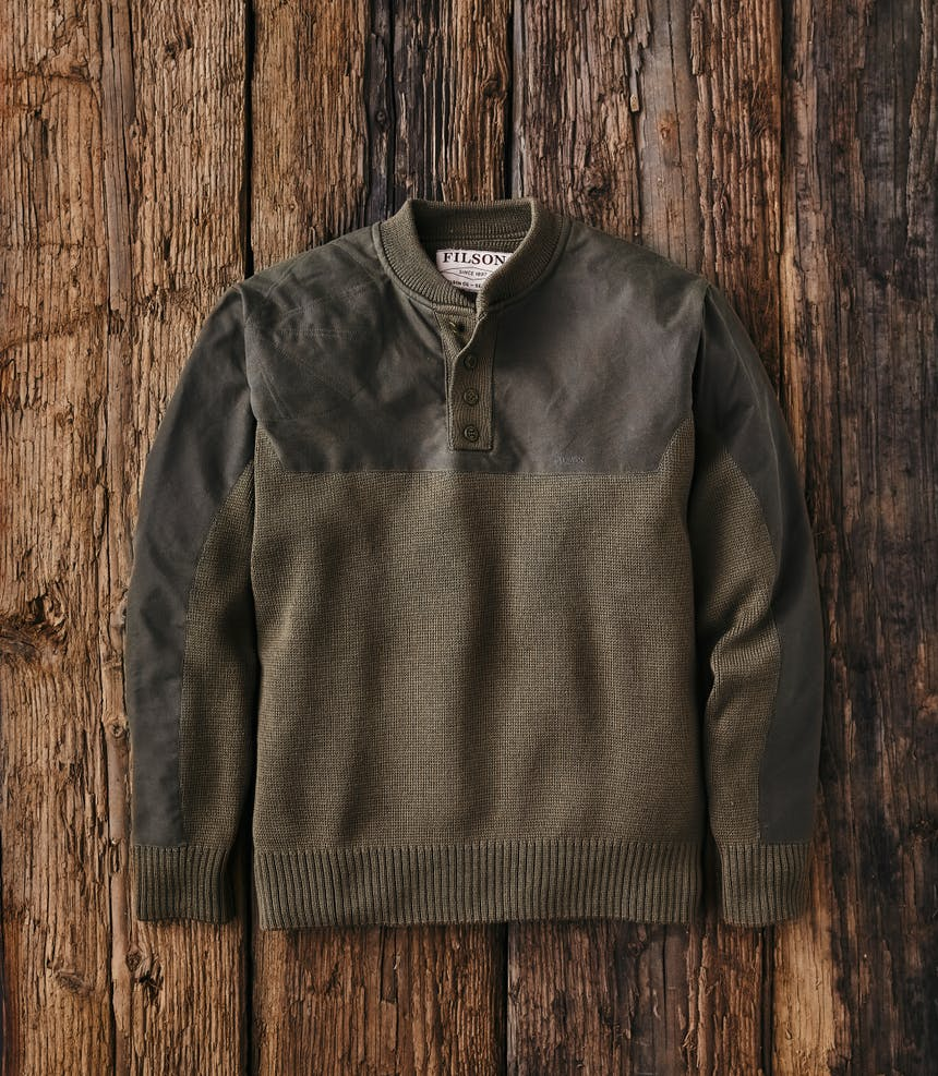 a top down view of a green merino wool pullover laid down on rustic wood