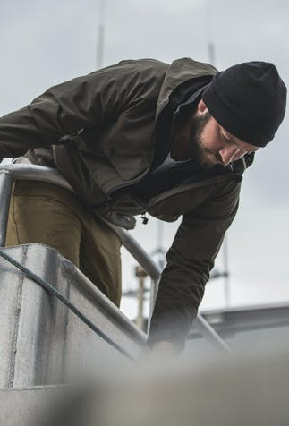 brunette man with full beard, wearing a brown rain coat, tan pants and a brown beanie leaning over the edge of a bow reaching for the rope line