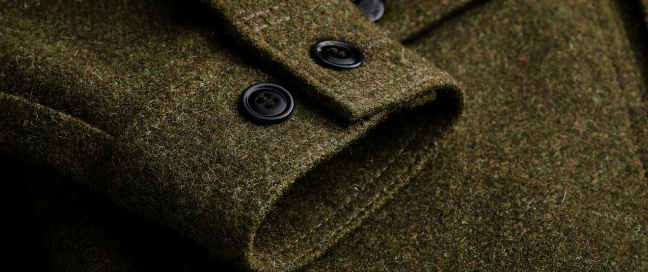 a close up of the cuff of a green mackinaw wool cruiser showing the stitching, black buttons and texture of the wool