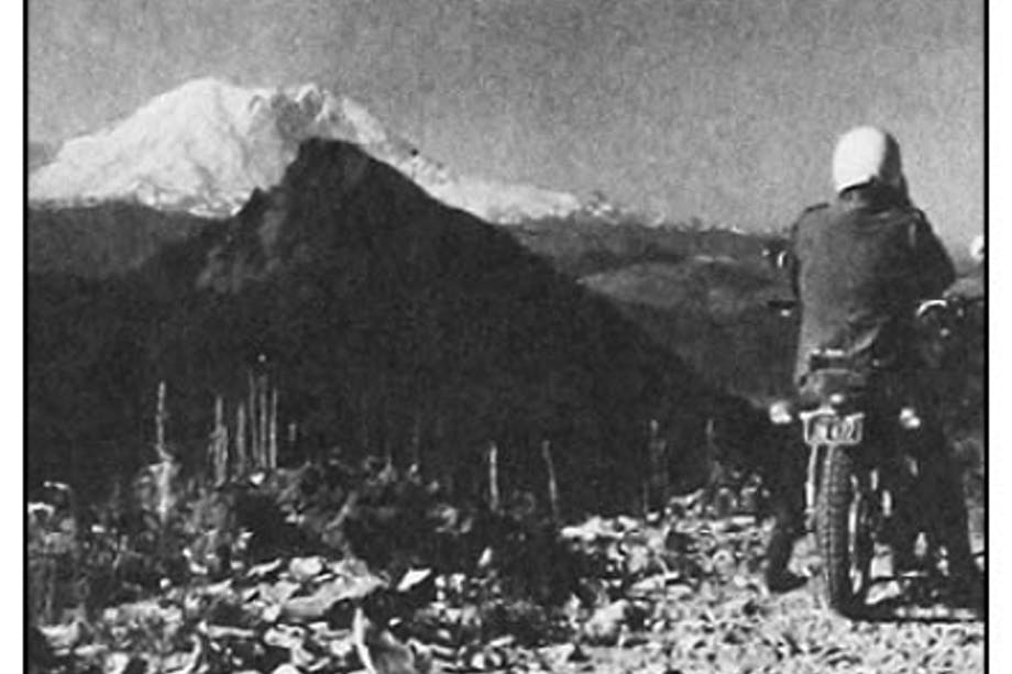 Grainy black and white image of man in white helmet and black coat looking out at large snow capped Mt. Rainier