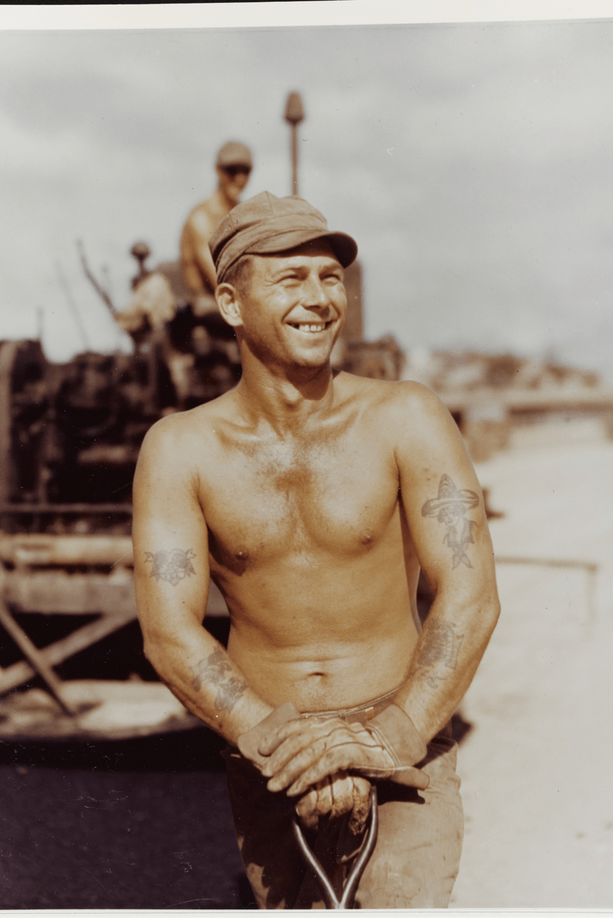 shirtless sailor with tattoos and brown hat stands on boat deck