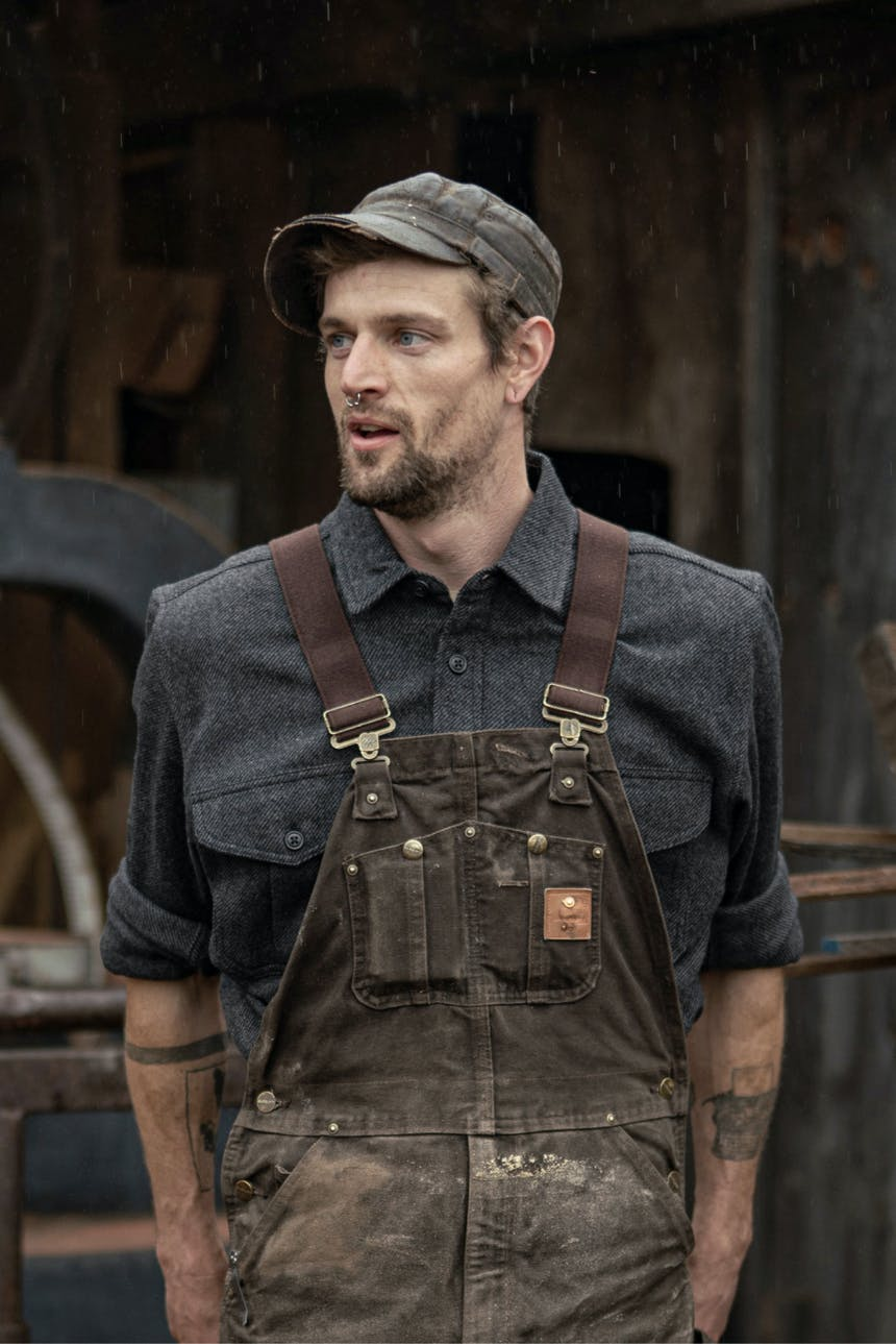 man in brown leather cap, blue buttonup shirt, and green overalls standing in front of a wooden wal